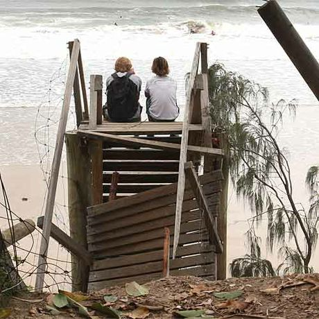 Surfers sit atop stairs damaged as result of swells and erosion caused by Cyclone Hamish. Photo:Nicholas Falconer/181397