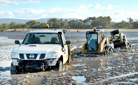 Two bobcats, middle and right, sent to rescue the stranded Nissan ute, left, were claimed by a similar fate on treacherous tidal flats at Armstrong Beach. High tides then put metres of salt water over the stranded vehicles.