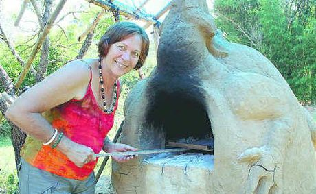 Robyn feeding the dragon, a wood-fired oven made from mud, sand and bamboo leaves.