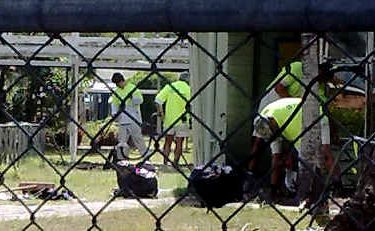 Painters use a vacuum cleaner to remove asbestos-contaminated paint flecks at Mackay West State School.