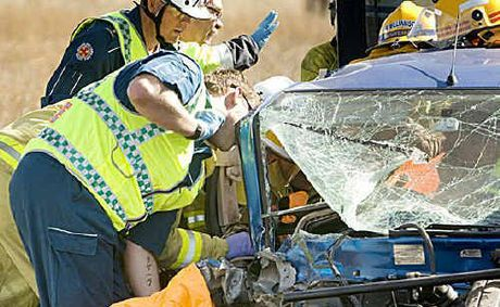 Paramedics attend to the trapped woman involved in the crash on the Warrego Highway yesterday.