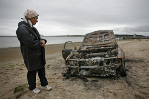 Burnt out car at Omokoroa beach. Vibeke Frolund inspects the damage. Photo: Sam Ackland.