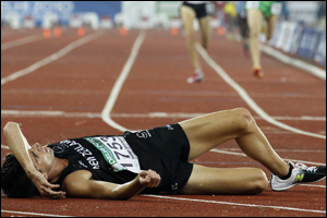 New Zealand's Adrian Blincoe lies on the track after the men's 5000m final. Photo: AP.