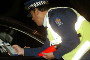 A driver gives a breath sample to a police officer at a checkpoint. Photo: Dean Purcell/File.
