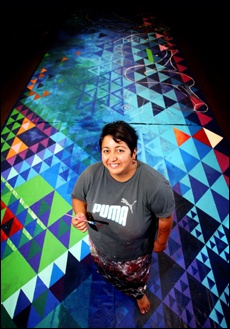 PICTURE CLAIRE DE BARR:  Artist Chanz Mikaere is painting the back drop for the stage.