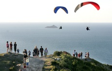 PICTURE: MARK McKEOWN: Two paragliders hover over some of the 350 strong crowd.