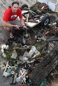 Shane Wasik with the haul of garbage divers pulled from the waters of Pilot Bay.