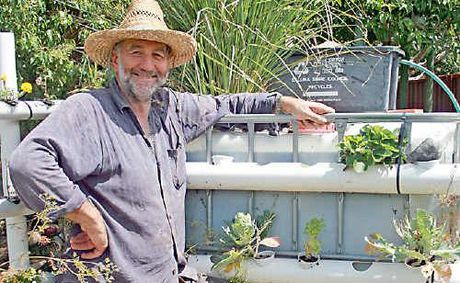 Wayne Wadsworth with his aquaculture tank in the backyard of the Reversing Greenhouse House in Goonellabah.