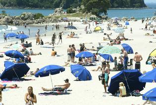 Beach crowds enjoying the sun at Mount Maunganui.