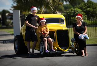 Tauranga Toy Run organiser Sarah Ellis (right) with her daughter Amber and Hot Rod owner Craig Jefferson.