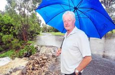 Paul Farmer watches the deluge erode away the newly repaired causeway at Arcadia Drive yesterday.
