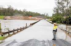 Bundaberg Regional Council roads maintenance officer Rick Green inspects the rising levels of floodwater that caused the closure of the Bruce Highway at the Isis River Bridge yesterday.