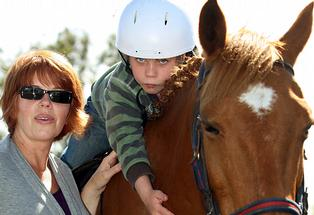 Caleb Richards, 8, atop his favourite horse, also named Caleb, pictured with Mum Nicola Richards.