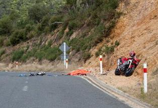 Police inspect the scene on SH25 where two motorcyclists collided, killing one and critically injuring another.