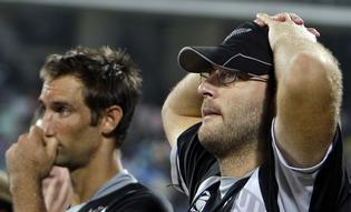 New Zealand's captain Daniel Vettori, right, and teammate Grant Elliot react after their loss in a one day international cricket match against India.