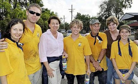 Lending a hand to clean-up flood devastated Queensland are (from, left) Svetlana Zaharova, Rolands Bricis, Queensland Premier Anna Bligh, Jason Best, Peter Dunn, Julie Attwood and Jessica Plattner.