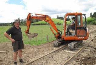 REPAIR WORK:Track supervisor Denis Hewitt, of Whangarei, checks progress on railway repairs as digger driver Mike Ngatoki clears the last of the flood debris.