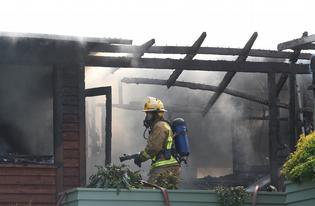 A firefighter keeps an eye on the dangers of a house destroyed by fire yesterday.