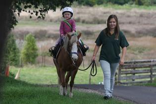 Horse riding is a fun way for Lenore Pope, 4, to get the physio she needs to fight cystic fibrosis. She loves riding Missy, lead by Evita Pill.