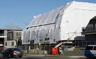 Marine Parade has been blighted with apartment buildings enveloped in plastic wrap for more than a year.