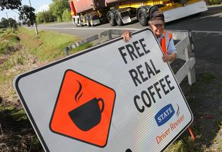 DOING HIS BIT: Northland Road Safety Association member Robyn Lilley puts up a sign for one of Northland&#39;s very successful &quot;driver reviver&quot; or Coffee Brake stops.