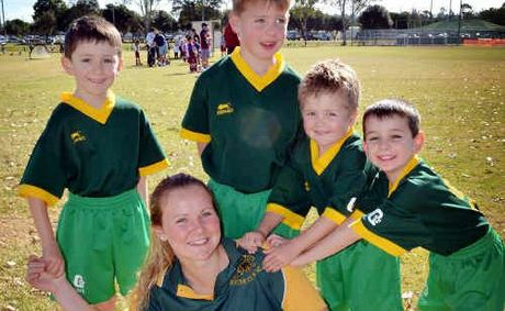 Golden City under-6 players George Pink, Camden Scott, Tate Verrills and Jonathon Seed try to hang on to their Norwegian coach Carina Hallgren.