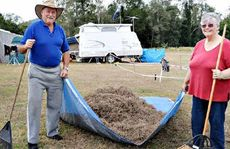 Stewart and Annette Muir rake their site before setting up camp at Amamoor.