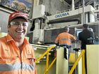 Terry Purcell, owner of Purcell's Lineboring and Engineering, Helen St, Gladstone, stands in front of a OKUMA Bridge Mill.