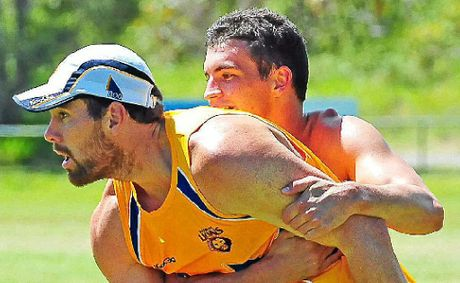 Brisbane Lions player Tom Rockliff wraps up Brisbane Lions recruit Ben Hudson as they train at Noosa.