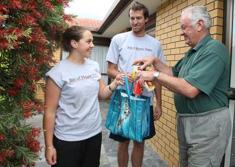 Bay of Plenty Times reporter Genevieve Helliwell and Richard Saunders collect cans of food from Ross Linney at his home in Mount Maunganui.