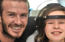 David Beckham poses for a picture with a girl at Royal Melbourne Children&#39;s Hospital.