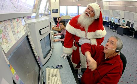 Air traffic controller Les Haynes shows Santa the route he will take when he flies through Australian airspace on Christmas Eve.