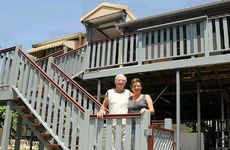 Fred and Karen Hewerdine outside their rebuilt Woolooga home yesterday.
