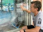 SHATTERED: Low Pressure Surf Co's Noel Smith inspects the damage to the pane of glass at the front of his shop after a vandal attack. Photo: Emma Pritchard