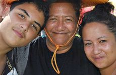 Trent Pere and Teshia Renata share some shade with their aunty Sharon Makea at Waitangi Day celebrations.