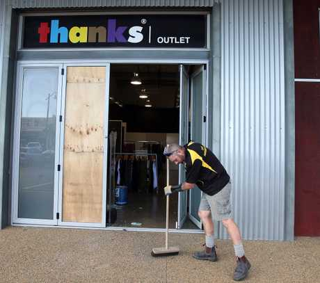 Glass is swept up from the Thanks clothing store after it was burgled early yesterday morning.