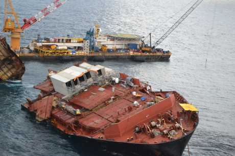 Containers can be seen pushing open the hatch covers on the bow section of the Rena.