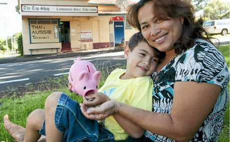 HELPING OUT: Kali Stack, 6, cheers up his mum Janya by giving her his piggy bank money after the family's shop was robbed.