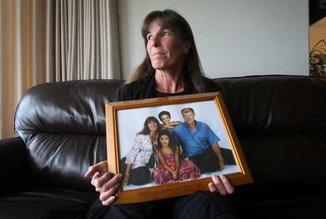 Sandi Clink holds a family photograph showing her deceased husband Andrew Clink. Also shown in the picture is daughter Aimee (8) and son Adam (6). 
