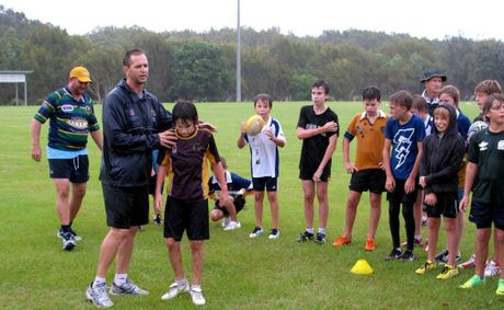 Gary Belcher tackle-trains Casuarina Beach Junior Rugby boys while under-11s coach Phil Brown, left, joins in with interest.