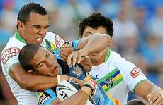Gold Coast's David Mead is gang-tackled by Raiders opponents on Saturday.