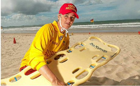 Sally Marx with a spinal board at Mooloolaba Beach.