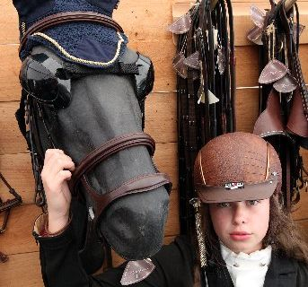 Orion Scott, 13, a Kapiti Coast girl , models the latest equestrian fashion - an Italian imported jacket, faux crocodile skin helmet and diamante-encrusted whip, beside protective horse sunglasses and crocheted ear covers.