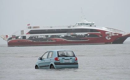 The Big Red Cat sails past the tourists&#39; car. The low tide and a GPS navigation system lured them into the bay at Oyster Point at Cleveland.