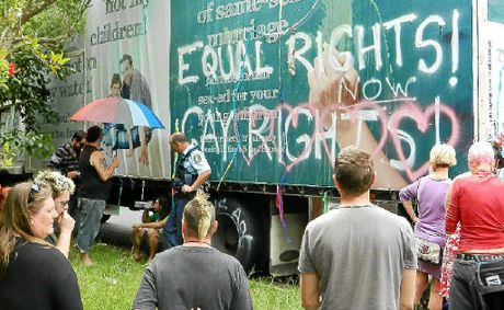 Protesters at the mobile billboard in Lismore on Sunday. Two people chained themselves to the truck and were released by Police Rescue.