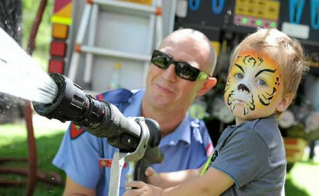 Blake Brown, 2, tries out a fire hose with firefighter Matt Rogers.