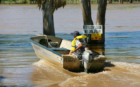 A man sets off from the Fitzroy River Motor Boat Club to tend to his boat moored on the river.