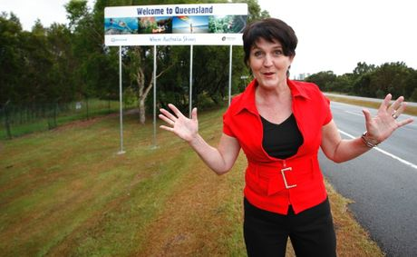 Minister for Tourism, Jann Stuckey poses for a portrait with a &#39;Welcome to Queensland&#39; sign.