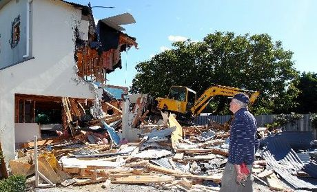 HEARTACHE: Devon Lee (above) watches as his Auckland Rd, Greenmeadows, leaky home is demolished after eight months of residency.