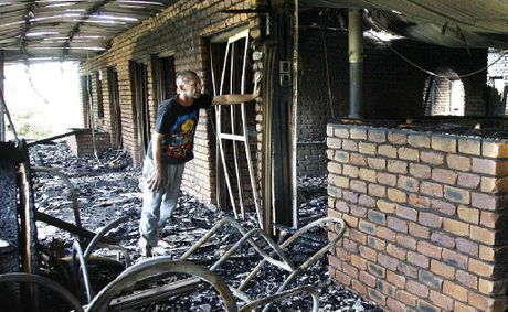 Brenden Reynolds surveys the wreckage of his father's burnt-out home.